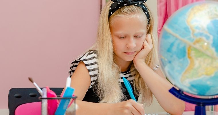 Young girl working at her desk at home