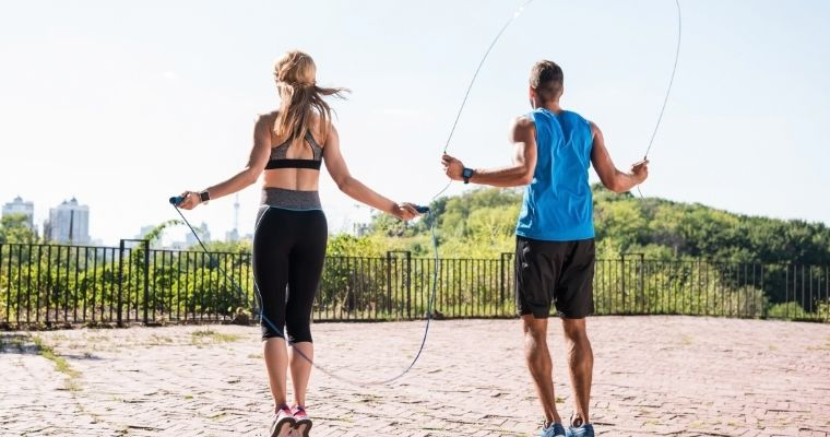 A man and woman using jump ropes outside