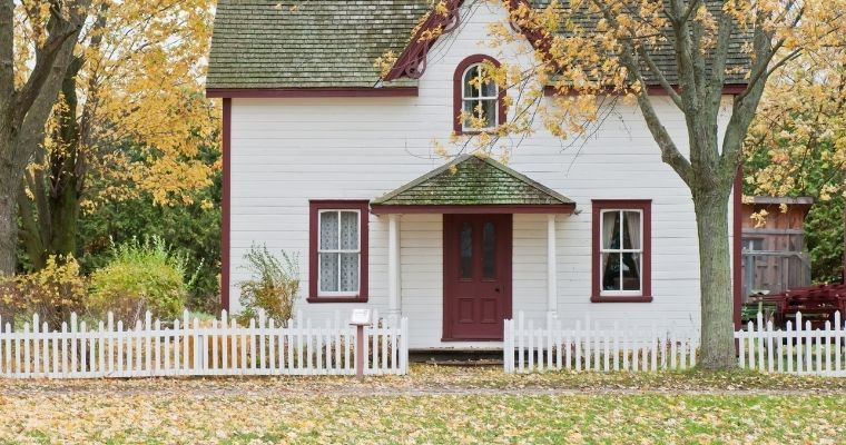 House surrounded by a picket fence set amongst trees
