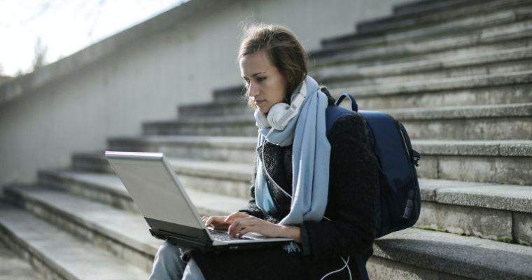 University student sat on steps using laptop