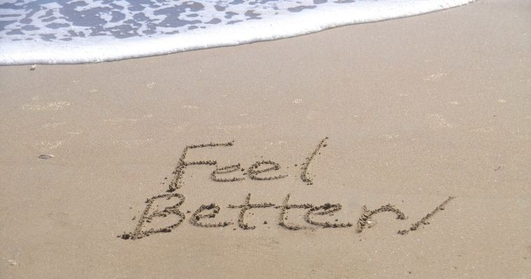 Writing in the sand on a beach saying Feel Better!