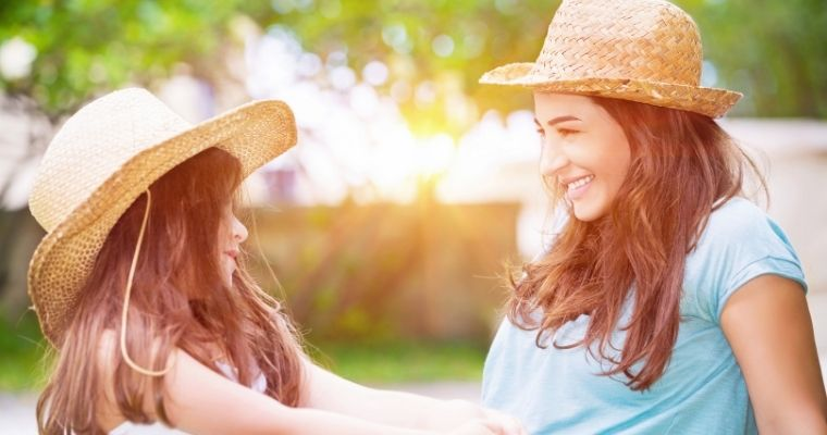 Mother and daughter sat outside chatting in the sunshine wearing straw hats