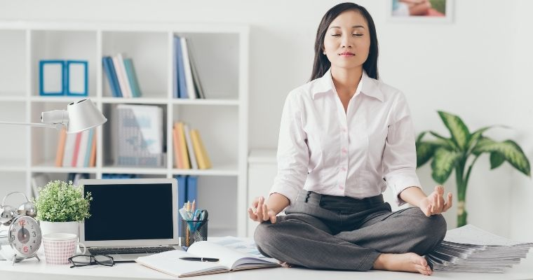 Woman meditating on her desk