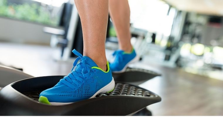 person standing on an elliptical trainer