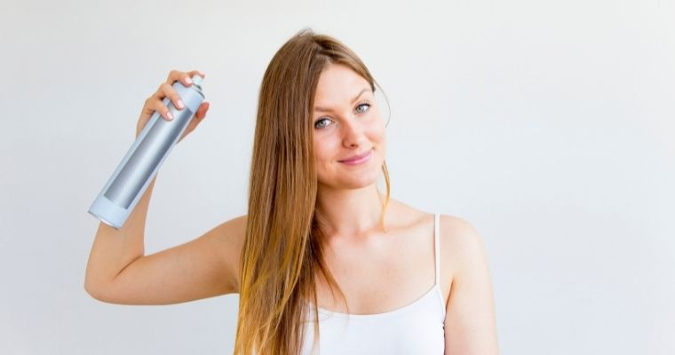 A young woman applying dry shampoo to her hair