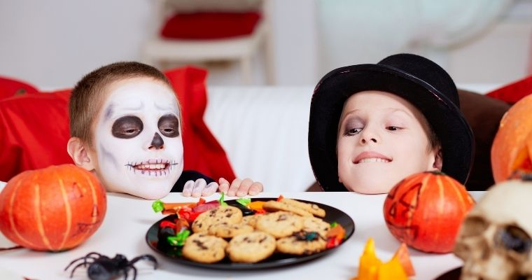 Two boys in Halloween costumes sat at a table looking at a plate of Halloween biscuits